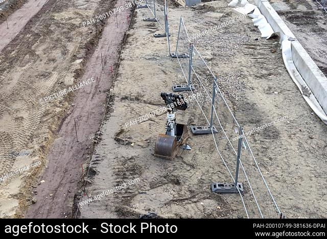 08 December 2019, Saxony-Anhalt, Magdeburg: View of an excavator shovel lying in the sand at the tunnel construction site