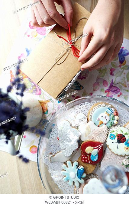 Woman tying a ribbon on a gift next to cakestand with cakes