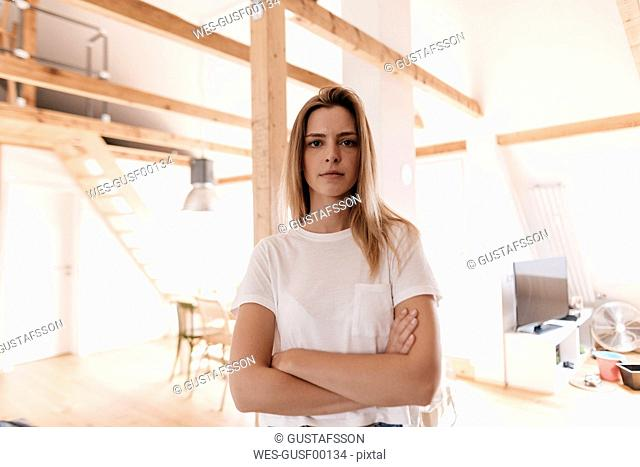 Confident young woman standing in her apartment with arms crossed