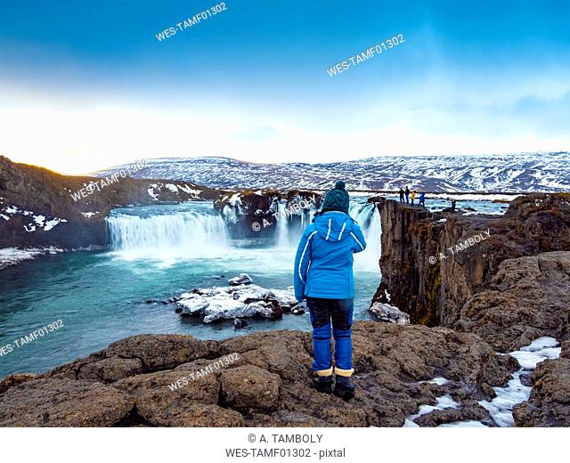 Iceland, woman at Godafoss Waterfall in winter