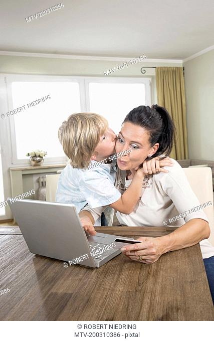 Boy kissing his mother while she online shopping on laptop, Bavaria, Germany
