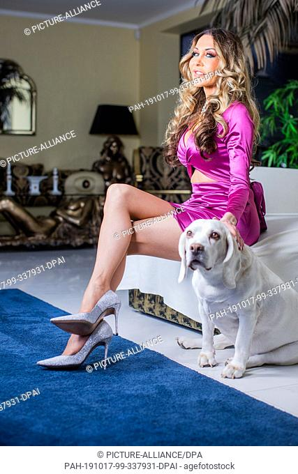 17 October 2019, North Rhine-Westphalia, Wesel: Dolly Buster, painter, author and former erotic actress, sits with her dog in the living room of her house