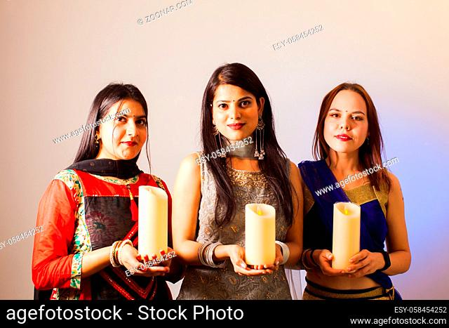 Portrait of three women in colorful sari dress holding lighted candles, looking at the camera. Indian girls caring their national traditions throug distance