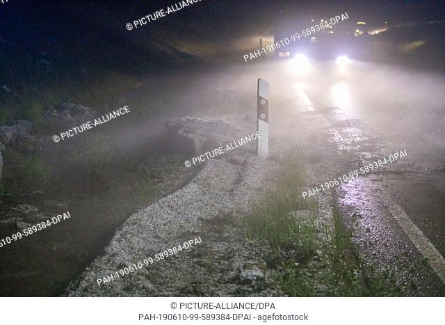 10 June 2019, Germany (German), Marienberg: Hail and a lot of rainwater complicate the traffic on the B 174 near Marienberg after a violent thunderstorm
