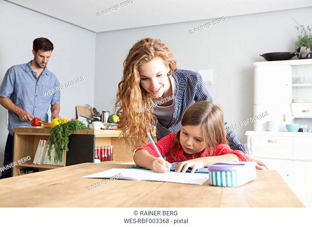 Little girl doing homework at the kitchen table with her parents in the background