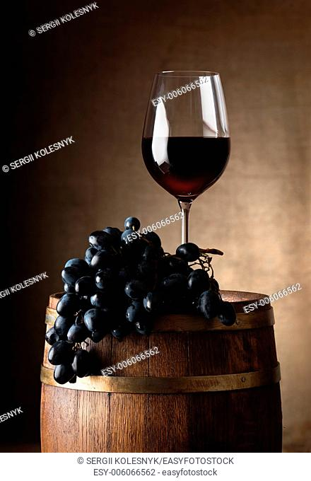Wine goblet with wooden barrel and grape