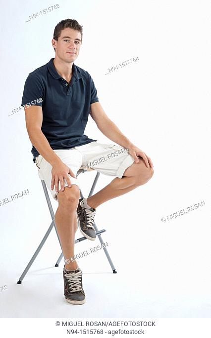 Full-body photograph of a teenage boy sitting on a stool