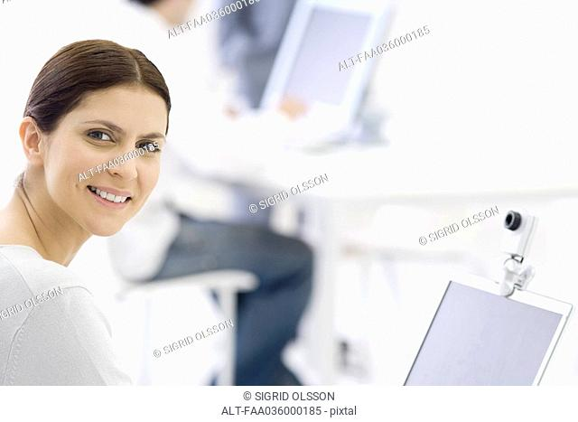 Woman in office, smiling over shoulder at camera