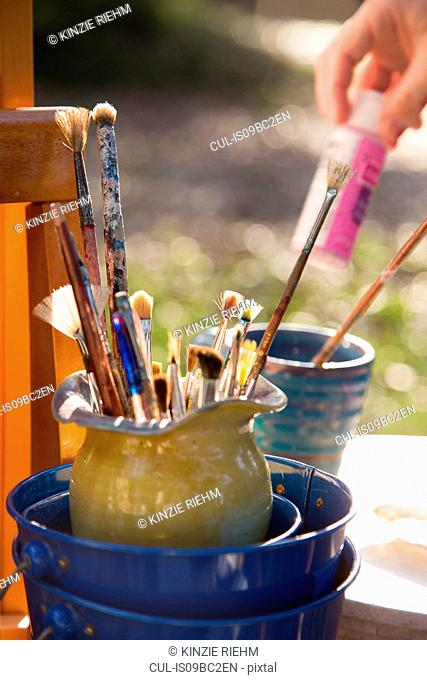 Paint brushes in jug and girl selecting paint in garden, close up of hand