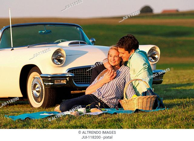 Couple Enjoying Countryside Picnic Next To Classic Car