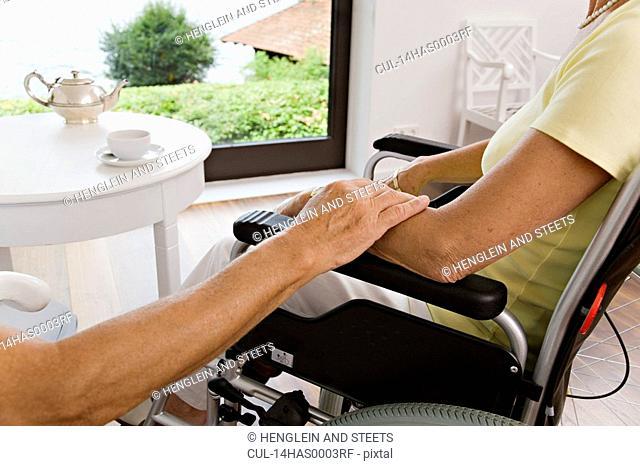 man touching woman in wheelchair