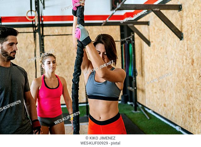 Athletes watching woman climbing a rope in gym
