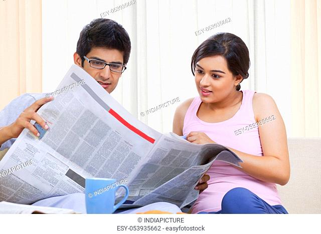 Young Indian couple reading newspaper together