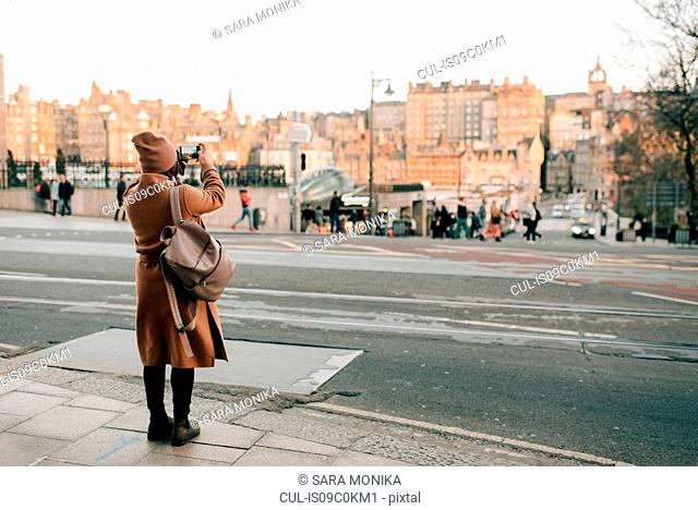 Woman sightseeing and taking photo, Calton Hill, Edinburgh, Scotland