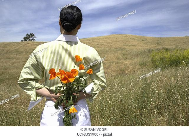 Woman holding bunch of flowers behind her back