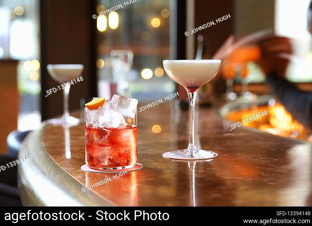 A Martini and a Negroni cocktail on the bar in a cocktail bar