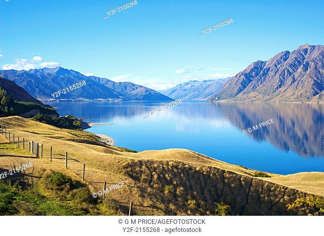 rugged hills and clouds reflected in Lake Hawea, New Zealand
