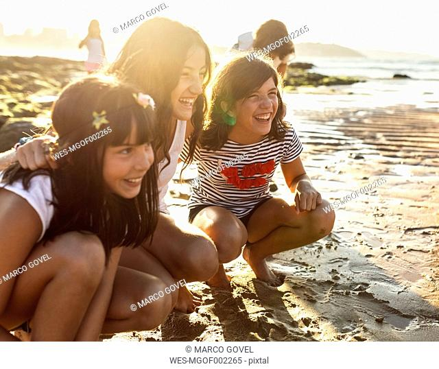 Three happy girls on the beach at sunset