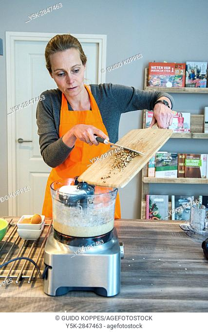 Kaatsheuvel, Netherlands. Mid adult caucasian woman preparing to bake a cake inside her residential kitchen