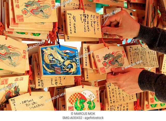 Hands holding wooden plaques with fortunes written on them at Shinjuku Park Shrine, Japan