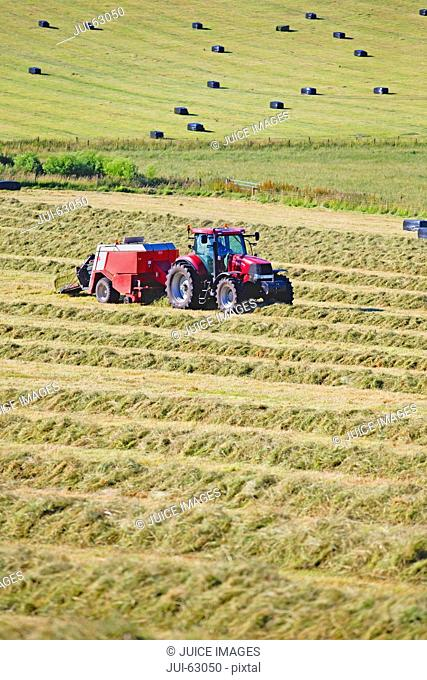 Tractor baling hay in field