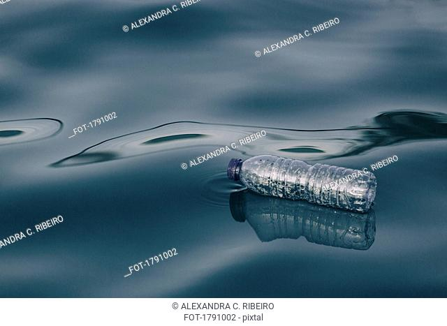 Plastic water bottle floating on water surface