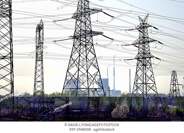 Chinese coal powered electricity generating power station on north side of city of Taiyuan, China. Cooling towers and grid pylons