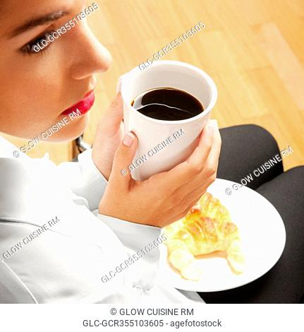 Woman sitting with a cup of coffee and plate of croissants