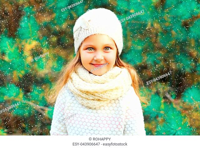 Little girl child wearing knitted hat sweater with scarf near christmas tree