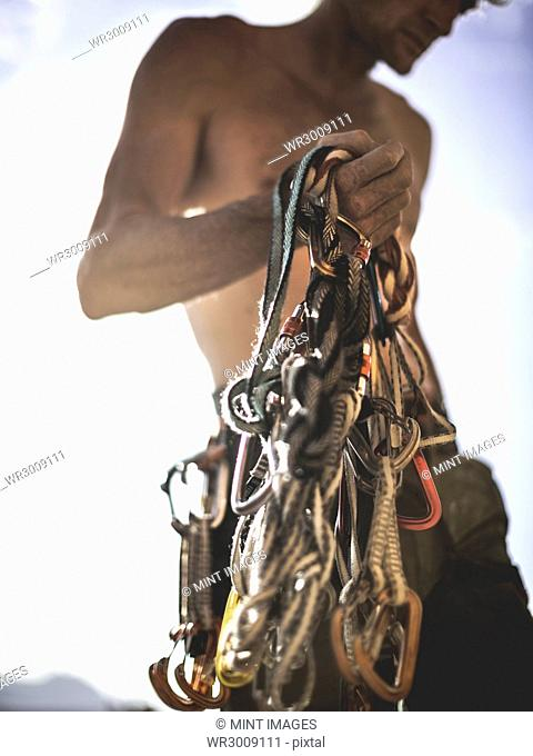 Close up of a climber holding a bundle of rope and carabiners, climbing equipment