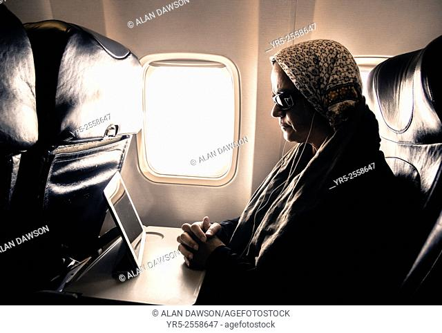 Woman watching movie on tablet device in window seat on airplane