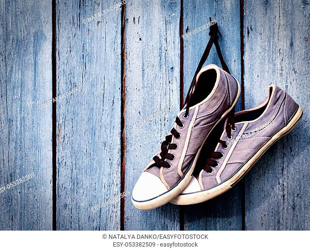 pair of old man's dirty blue sneakers hanging on a wooden wall, empty space