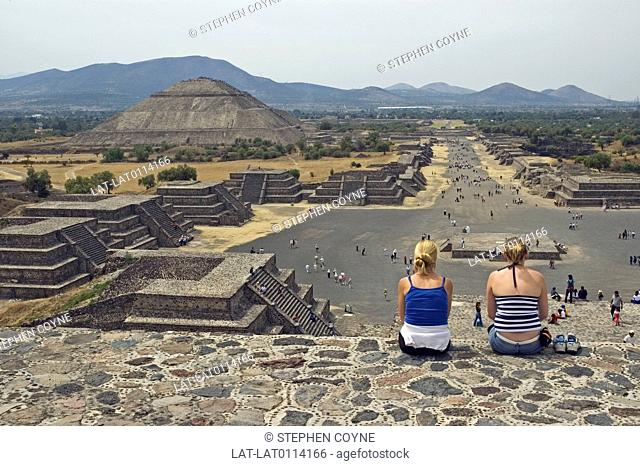Large archaeological Axtec site. Built in 1st century AD. Two young women sitting on top of a structure. Pyramid of the Moon viewing the Pyramid of the Sun and...