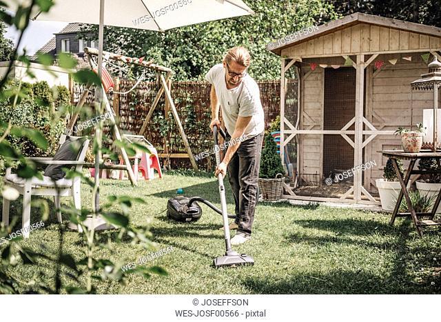 Man hoovering lawn in garden