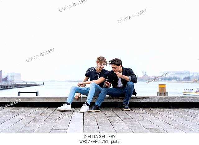 Denmark, Copenhagen, two young men sitting at the waterfront using cell phone