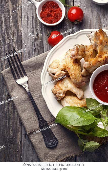 Top view on plate of grilled chicken wings served with tomato deep and fresh basil over old wooden table