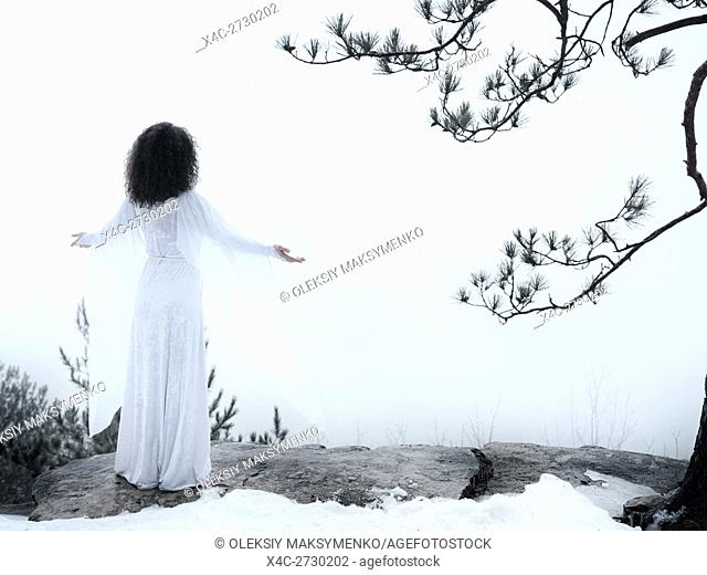 Woman in white dress standing on a cliff meditating with spread hands embracing the world and the nature. Spiritual concept