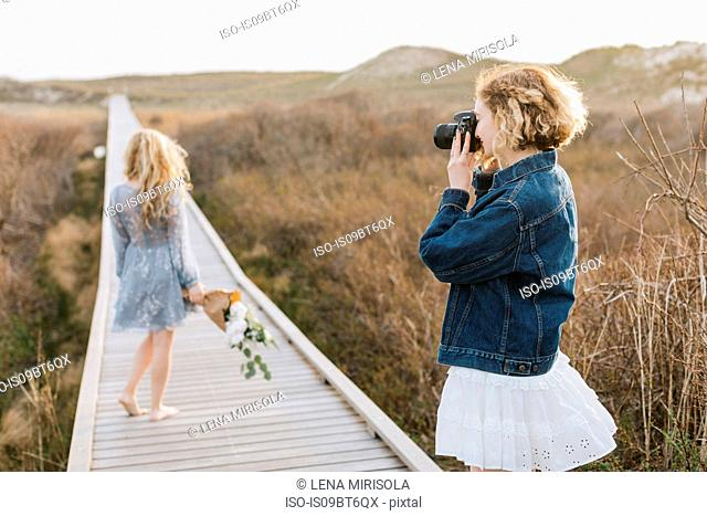 Young woman photographing friend on coastal dune boardwalk, Menemsha, Martha's Vineyard, Massachusetts, USA