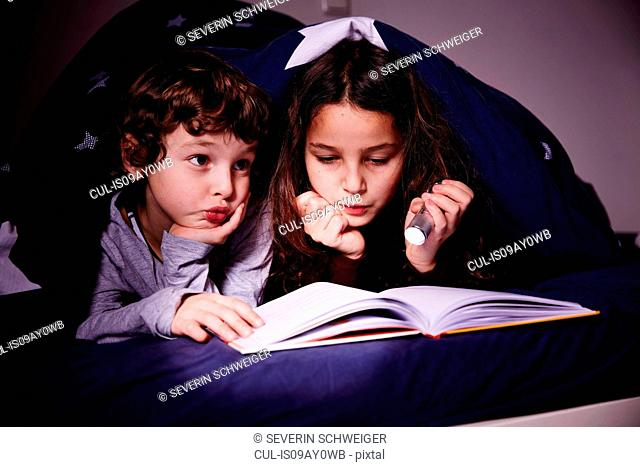 Brother and sister under duvet reading book by torchlight