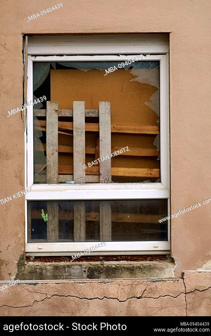 Bulky waste such as furniture and wood waste are behind a broken window
