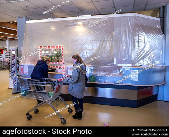 24 March 2020, Mecklenburg-Western Pomerania, Schwerin: Customers stand at the cash desk area in the trading yard in front of a temporary foil wall with a...