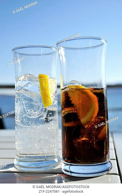 Two glasses filled respectively with a dark and transparent liquid