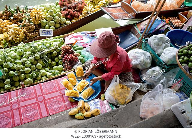 Thailand, Bangkok, Woman selling fruits on floating market