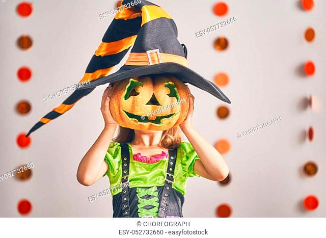 Happy Halloween! Cute little laughing girl in witch costume with a pumpkin