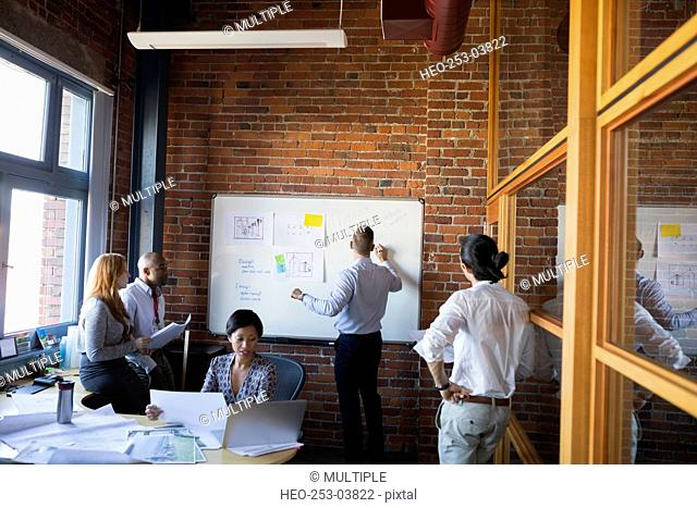Business people meeting at whiteboard in conference room