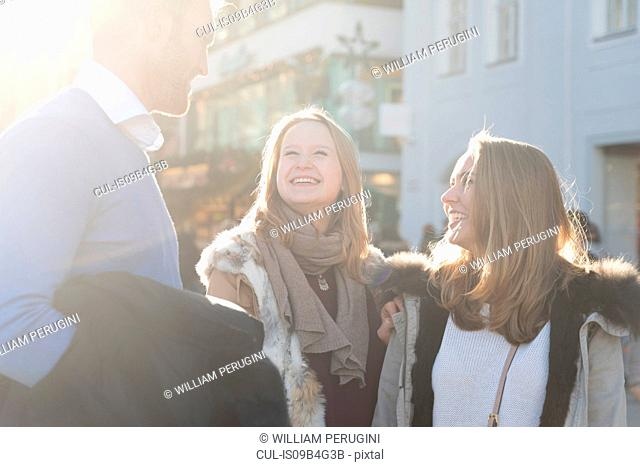 Young man and female friends chatting in sunlit city street