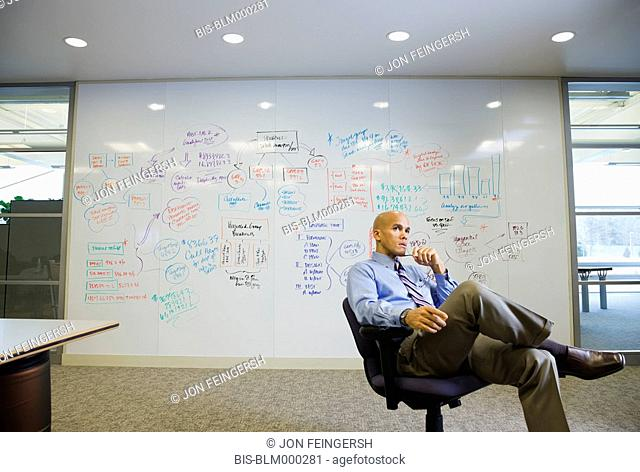 Mixed race businessman sitting in front of whiteboard