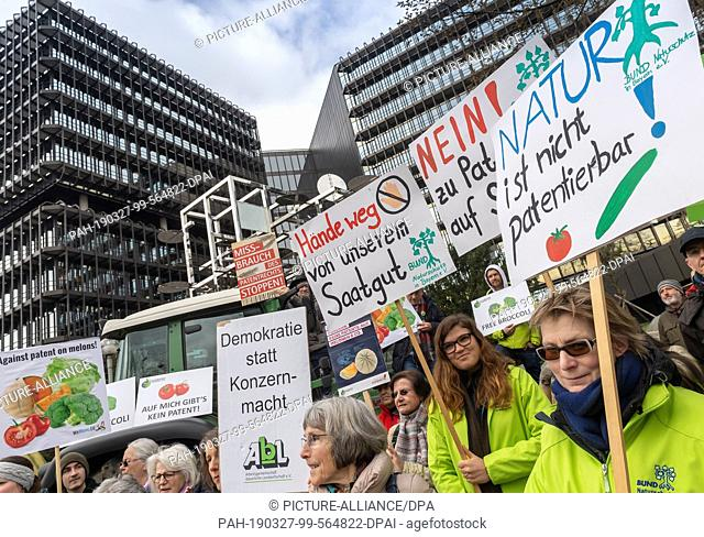 27 March 2019, Bavaria, München: Demonstrators take part in a protest action against patents on plants and animals with posters in front of the European Patent...