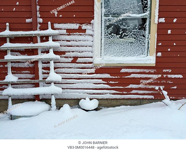 Snow collecting on the side of a red house after a winter storm