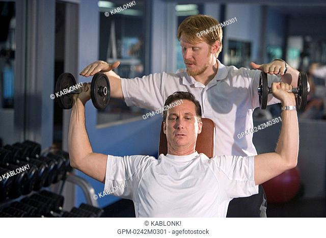 Mature man lifting weights at gym with assistance from personal trainer
